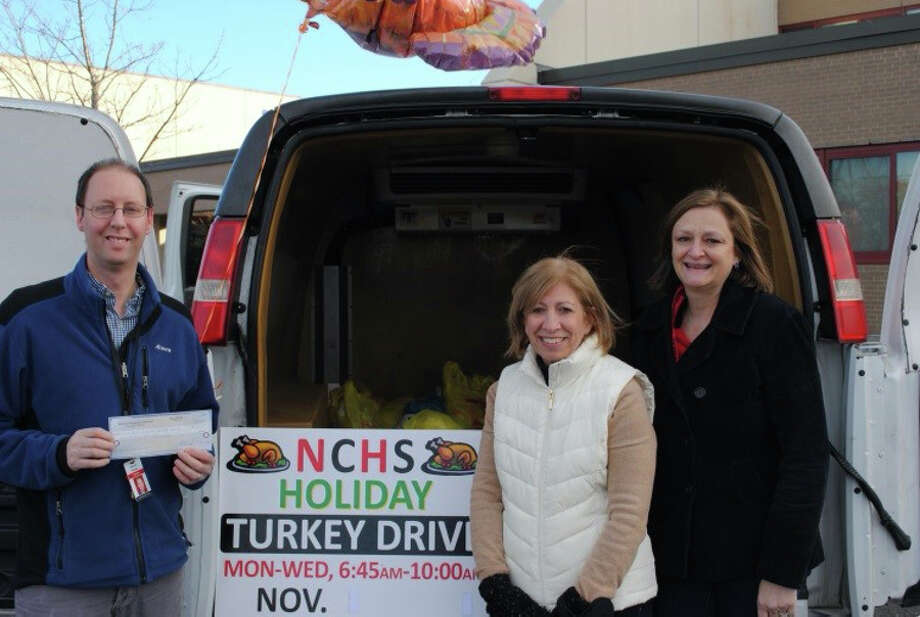 The New Canaan Education Association recently gave a check for $1,000 to the Food Bank of Lower Fairfield County. From left, Darren Bruce, New Canaan Education Association fundraising chairman; Ronna Van Veghel, NCEA vice president, and Vivian Birdsall, NCEA president, make a donation to the New Canaan High School Turkey Drive on behalf of the NCEA on Nov. 19. — Contributed photo