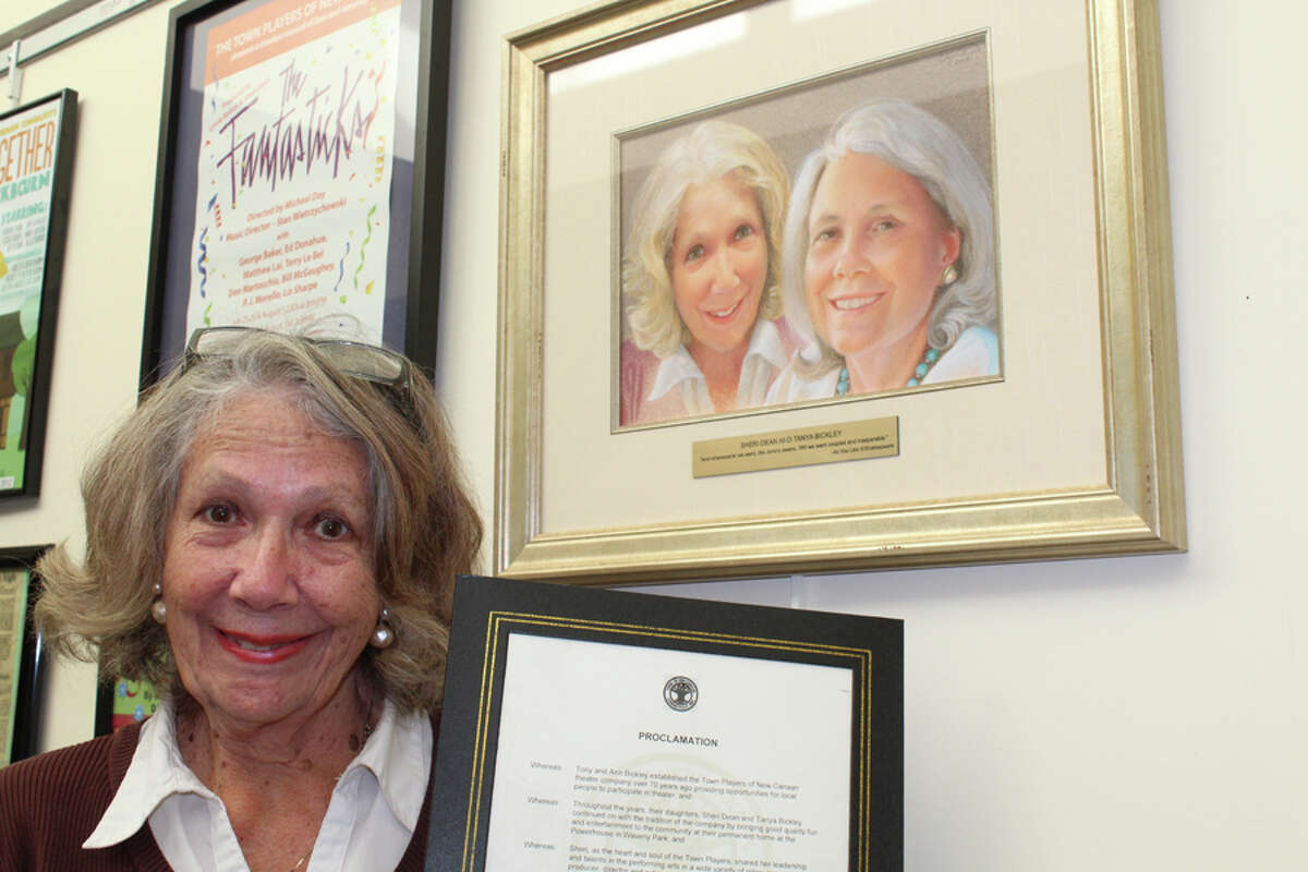 Sheri Dean holds a proclamation from the town honoring her while next to a portrait of the Town Players of New Canaan leader and her sister, the late Tanya Bickley, in the lobby of the Powerhouse Theatre in Waveny Park. Elizabeth Noble of Wilton painted the portrait. The frame includes a plaque bearing a quote from Shakespeare's As You Like It. -John Kovach photos