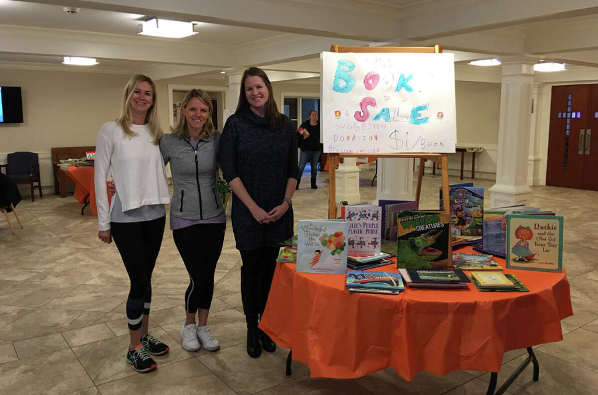 United Methodist Preschool in New Canaan recently held a book-swap in place of a normal book fair. United Methodist Preschool Parent Committee members, from left,  Liz McClave, Destiny Ikard and J.J. Russo set up the Book Swap. - Contributed photo