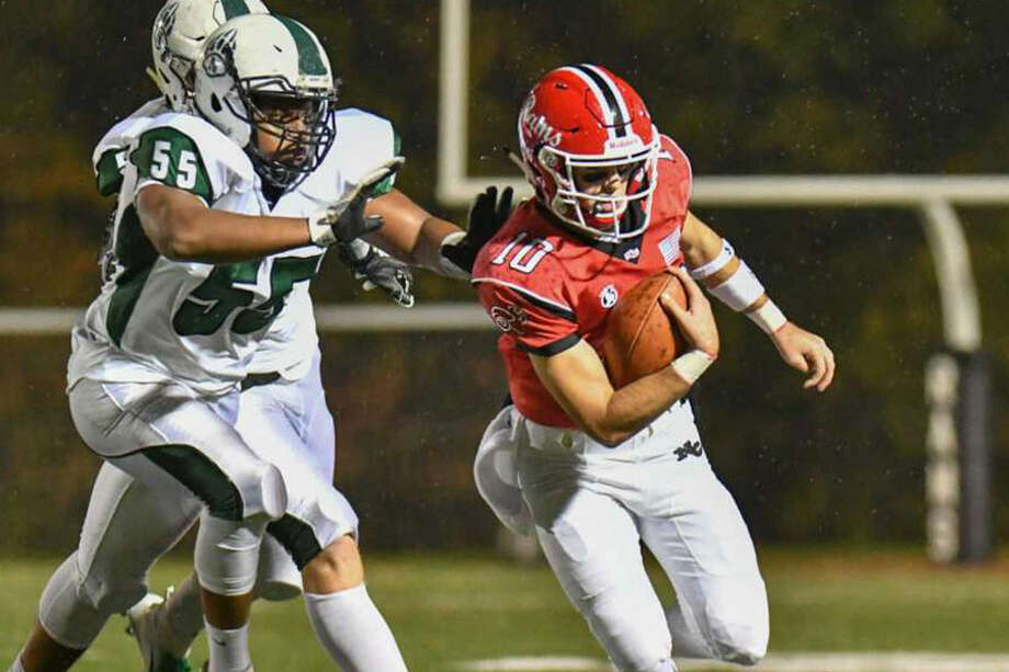 New Canaan QB Drew Pyne escapes from Norwalk's Aaron Epps during the Rams' 34-0 win Friday night at Dunning Field. — Gregory Vasil/Hearst Connecticut Media photo