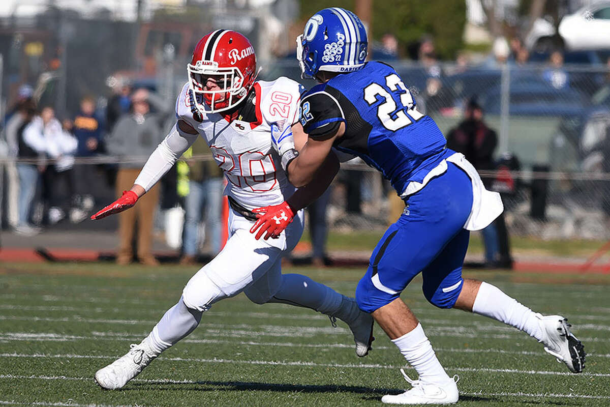 New Canaan's Quintin O'Connell (20) battles Darien's Connor Tienken, a 2018 graduate, during last season's Turkey Bowl game at Boyle Stadium. - Dave Stewart photo