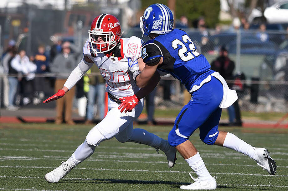 New Canaan's Quintin O'Connell (20) battles Darien's Connor Tienken, a 2018 graduate, during last season's Turkey Bowl game at Boyle Stadium. — Dave Stewart photo