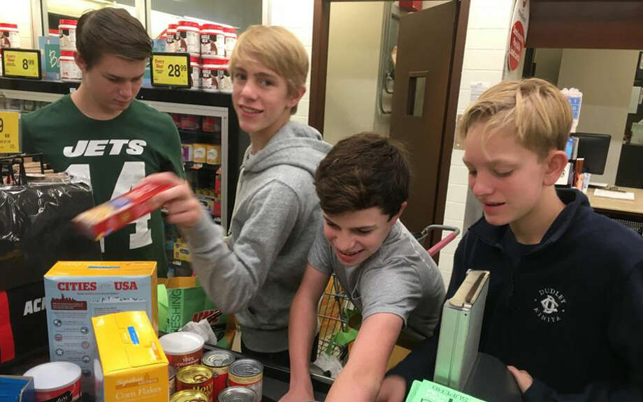 Youth from the First Presbyterian Church of New Canaan recently participated in a 30 Hour Famine. Participants, from left, Alexander Walker, Cal Stuart, Andy Dooley, and Gordie Stuart pack more than 25 bags of canned goods and other necessities that are needed most at the food pantry. — Contributed photo