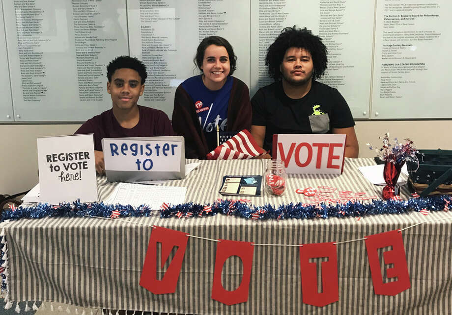 Scholars of ABC House, from left, Adrian Davis, sophomore, Jessica Stargardter, residential tutor, and Ryan Hernandez, senior, run a voter registration booth at New Canaan YMCA Oct. 29. — Contributed photo / Copyright 2018. All rights reserved.