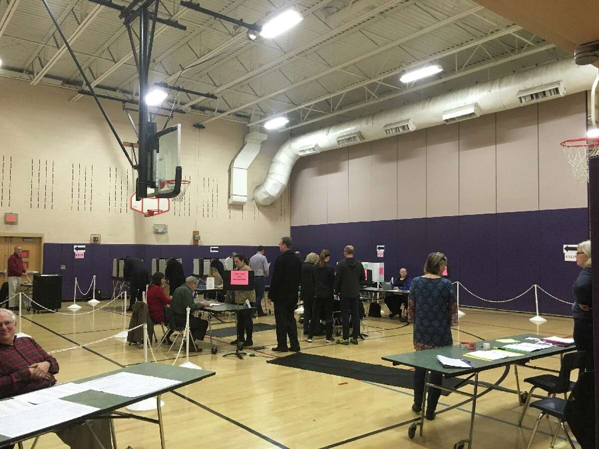 A clutch of poll workers and voters inside the Saxe Middle School polling place at 7:15 today - Election Day morning. - Greg Reilly photo