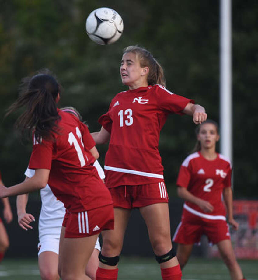 New Canaan's Olivia Bognon (13) goes up for a header. — Dave Stewart photo