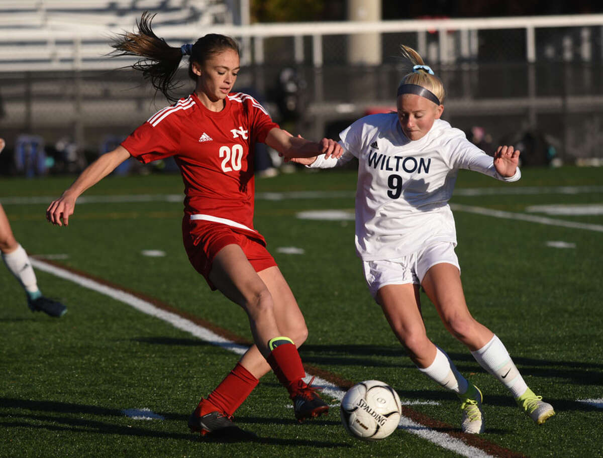 Ram sophomore Emma Schuh (20) battles Wilton's Piper Chase (9) during New Canaan's 1-0 win in the FCIAC quarterfinals last Thursday at Dunning Field. - Dave Stewart photo