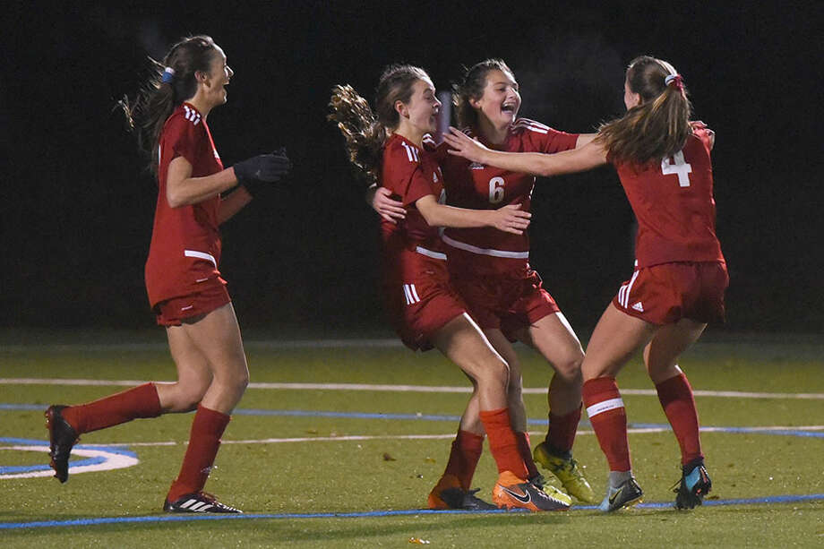 The New Canaan Rams celebrate one of their five goals during a 5-0 win over rival Darien in the FCIAC girls soccer semifinals Monday night in Wilton. — Dave Stewart photo