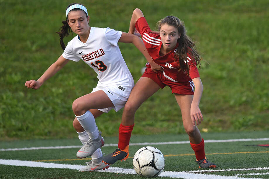 New Canaan's Dillyn Patten (right), and Ridgefield's Amelia Hynes (13) battle for the ball during the Rams' 1-0 win at Dunning Field on Saturday. — Dave Stewart photo