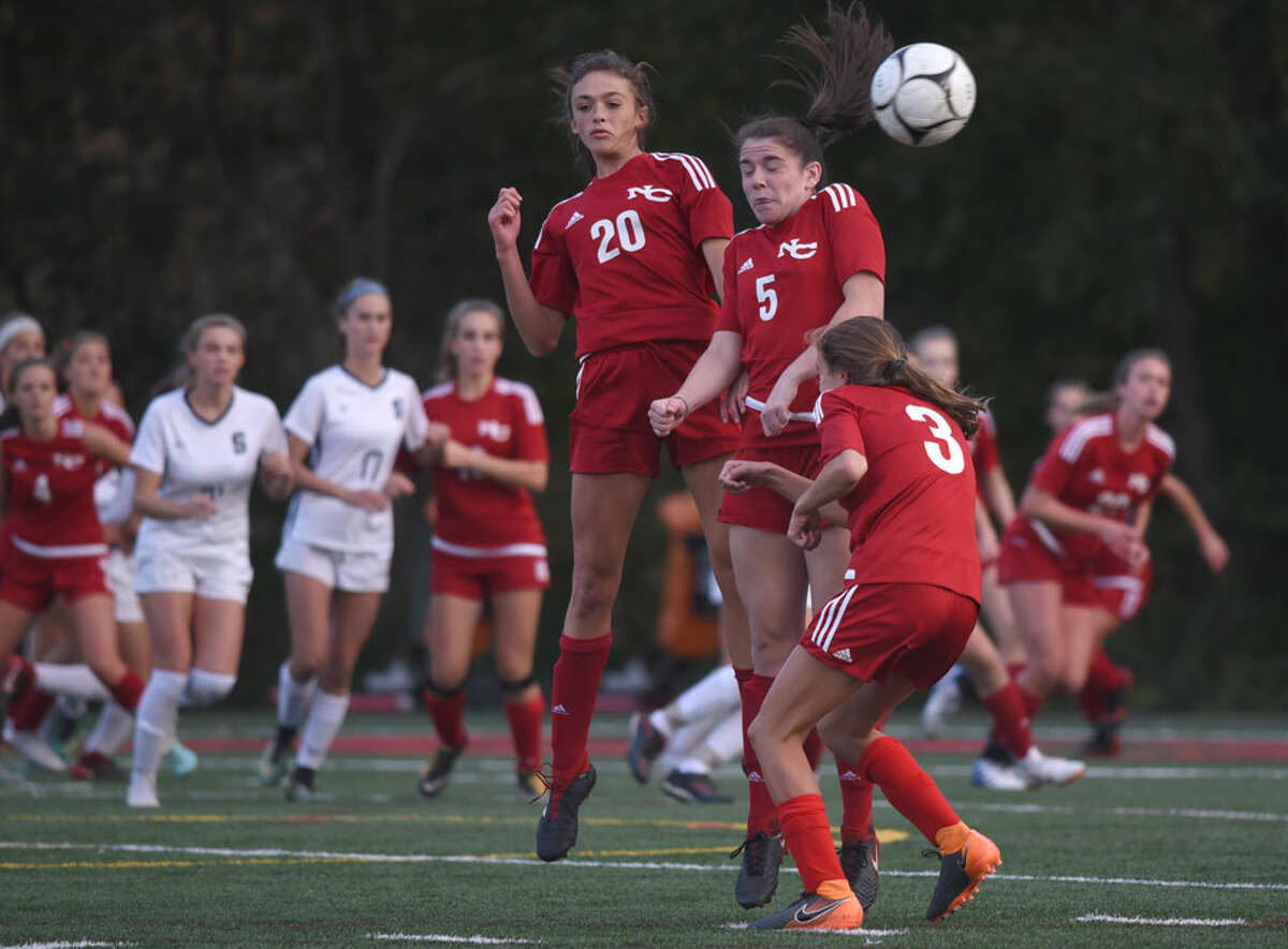 New Canaan's Emma Schuh (20), Elizabeth St. George (5), and Dillyn Patten (3) attempt to disrupt a Staples direct kick. - Dave Stewart photo