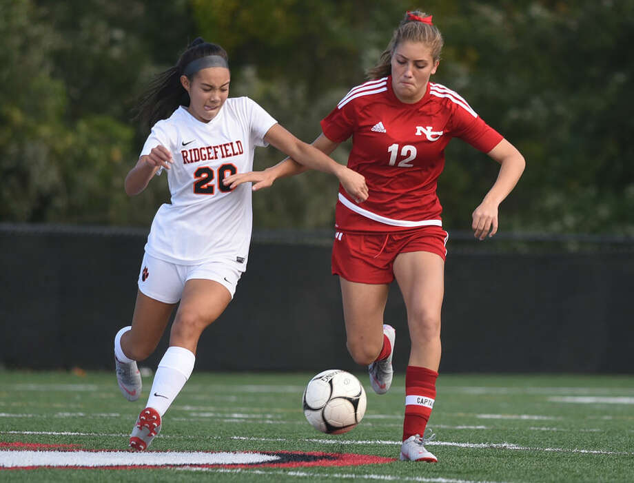 New Canaan senior co-captain Katelyn Sparks (12) goes head to head with Ridgefield's Julia Bragg (20). — Dave Stewart photo