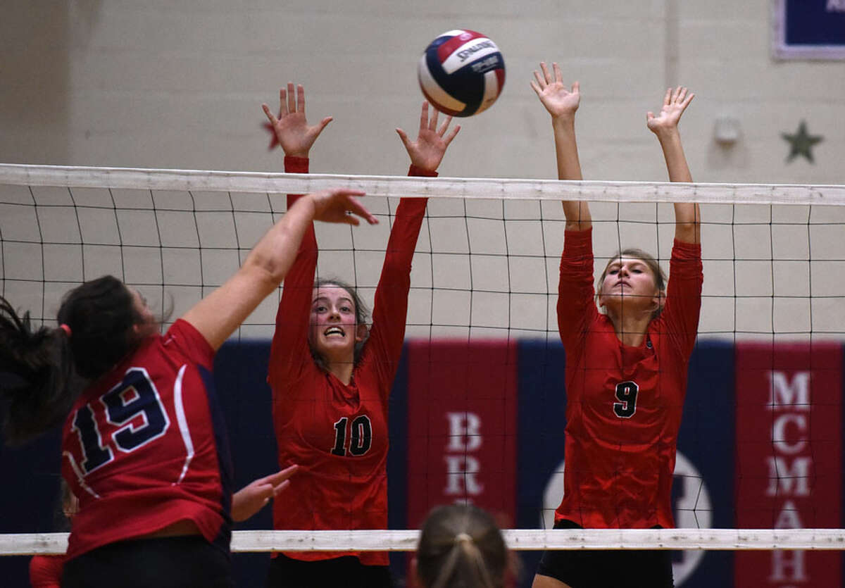 New Canaan's Alex Gillespie (10) and Ally Leopold (9) attempt to block a shot during a volleyball match at Brien McMahon on Oct, 12. - Dave Stewart photo