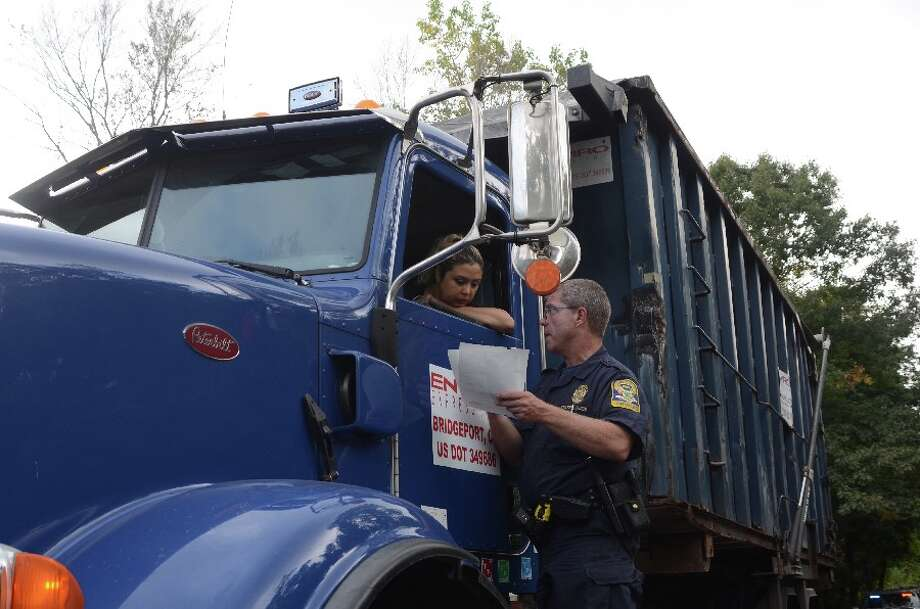 State Police trooper on Hoyt Farm Road on Oct. 10 explains an infraction as he delivers it to the driver of a truck with unsecured cargo. — Greg Reilly photo