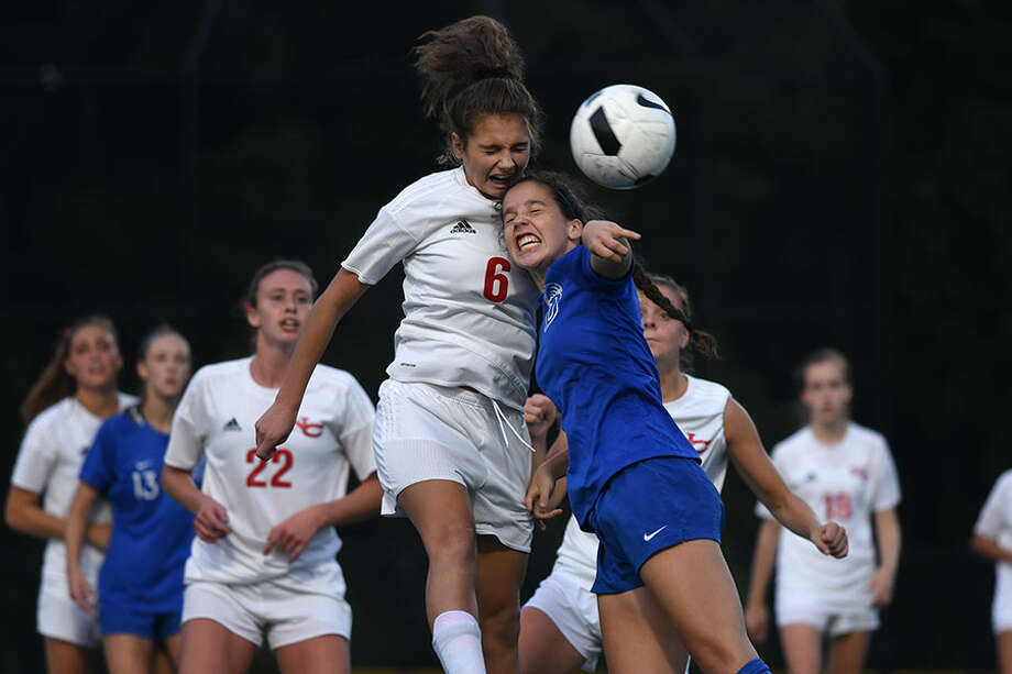 New Canaan's Kaleigh Harden (left) and Darien's Eilanna Dolan collide while going up for a header during Tuesday's rivalry game at DHS. The Rams edged ahead for a 1-0 win. — Dave Stewart photo