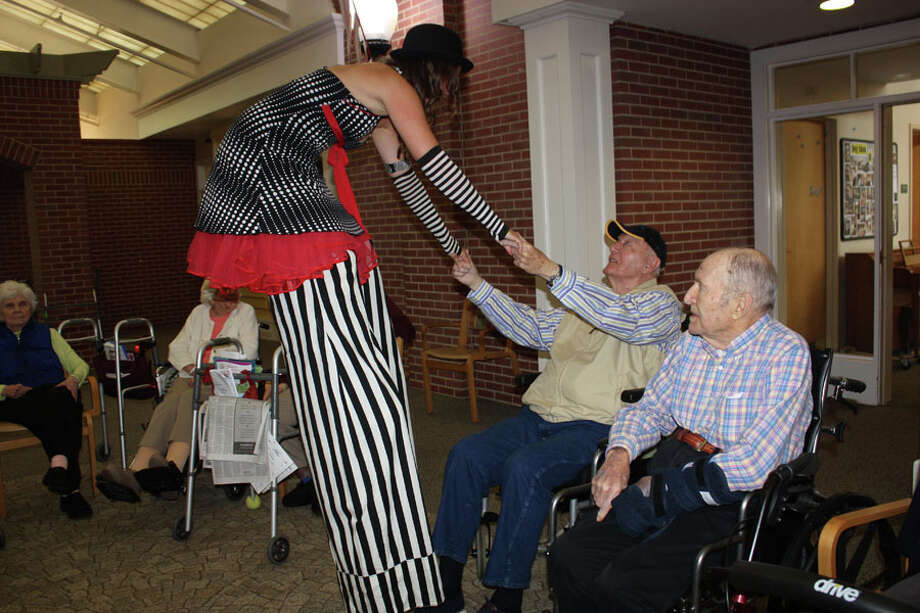 A professional stilt walker entertains an audience member. — Contributed photo