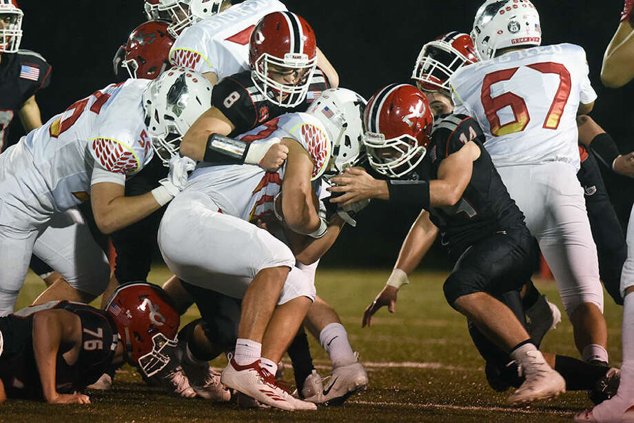 New Canaan's AJ Rakoczy (8) and Jack Defrancesco (14) wrap up Greenwich's Tysen Comizio (40) during Saturday night's football game at Dunning Field. — Dave Stewart photo