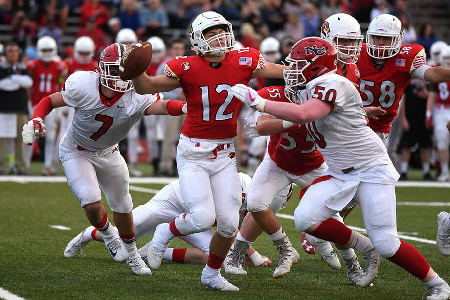 The New Canaan defense chases down Greenwich quarterback Gavin Muir during last year's football clash at GHS. — Dave Stewart photo