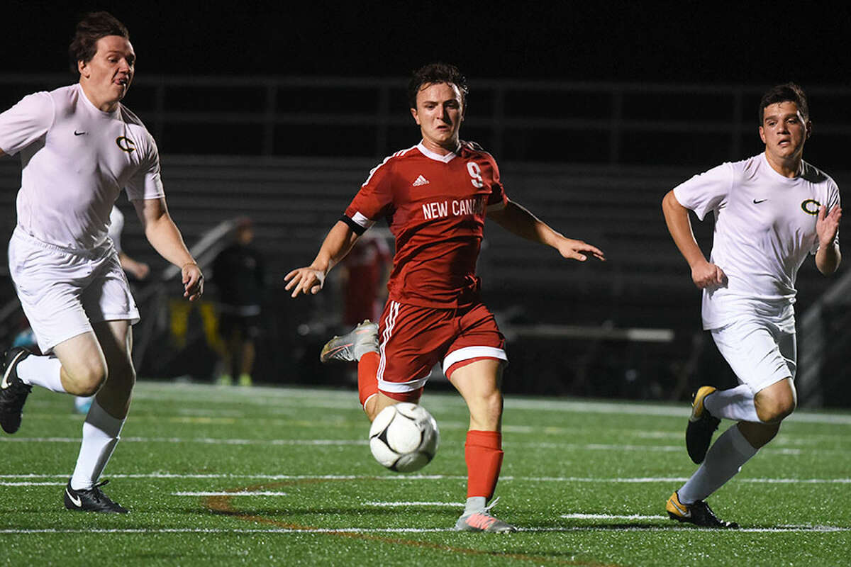 New Canaan's Timothy Norton chases down the ball in front of a pair of Trinity Crusaders during Monday night's boys soccer game at Dunning Field. - Dave Stewart photo