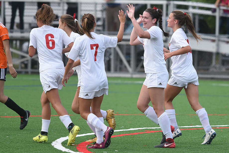 New Canaan's Elizabeth St. George high-fives teammate Olivia Cosco (7) after scoring her third goal in New Canaan's 6-0 win Thursday in Stamford. — Dave Stewart photo