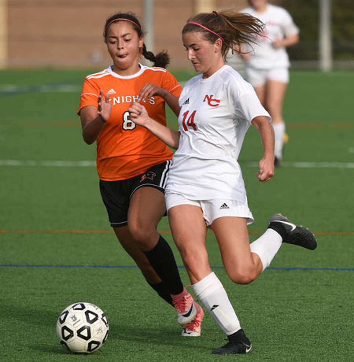New Canaan's Jackie Steele (14) gets to the ball ahead of Stamford's Francesca Ordonez. - Dave Stewart photo