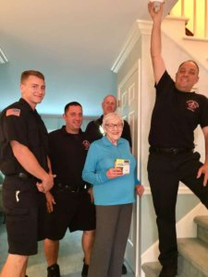 The New Canaan Fire Department offers free inspection, smoke alarms, and CO detectors. Firefighter Steve Gaeta replaces the expired smoke alarm in Staying Put member Katch Cerow's home.  Looking on are, from left, firefighters Will Garbus and Joe Dilorio, and Lt. Duffy Sasser. — Cathy Fitzpatrick photo