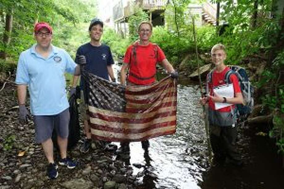 A Flag to rabbit ears, among hundreds of pounds of trash in a Five Mile River cleanup for a New Canaan Boy Scout Troop 70's fall Eagle Scout project. Tom Williams, right, of Boy Scout Troop 70, and volunteers hold an American flag they found during the recent river cleanup. — Contributed photo