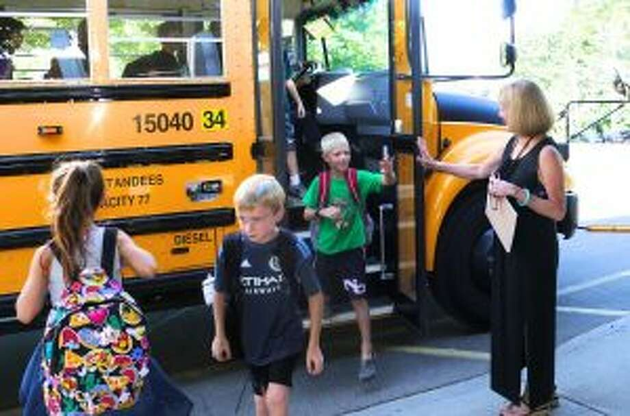 New Canaan: Public Schools principals have reflected on the first days of school. Principal Jan Murphy high-fives students as they get off the bus for their first day at West School. — Grace Duffield photo