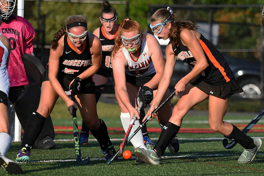 New Canaan's Meghan Mitchell battles a few Tigers in front of the Ram cage during a game at Dunning Field last fall. Mitchell returns as a senior co-captain this year, and will anchor a deep New Canaan defense. — Dave Stewart photo
