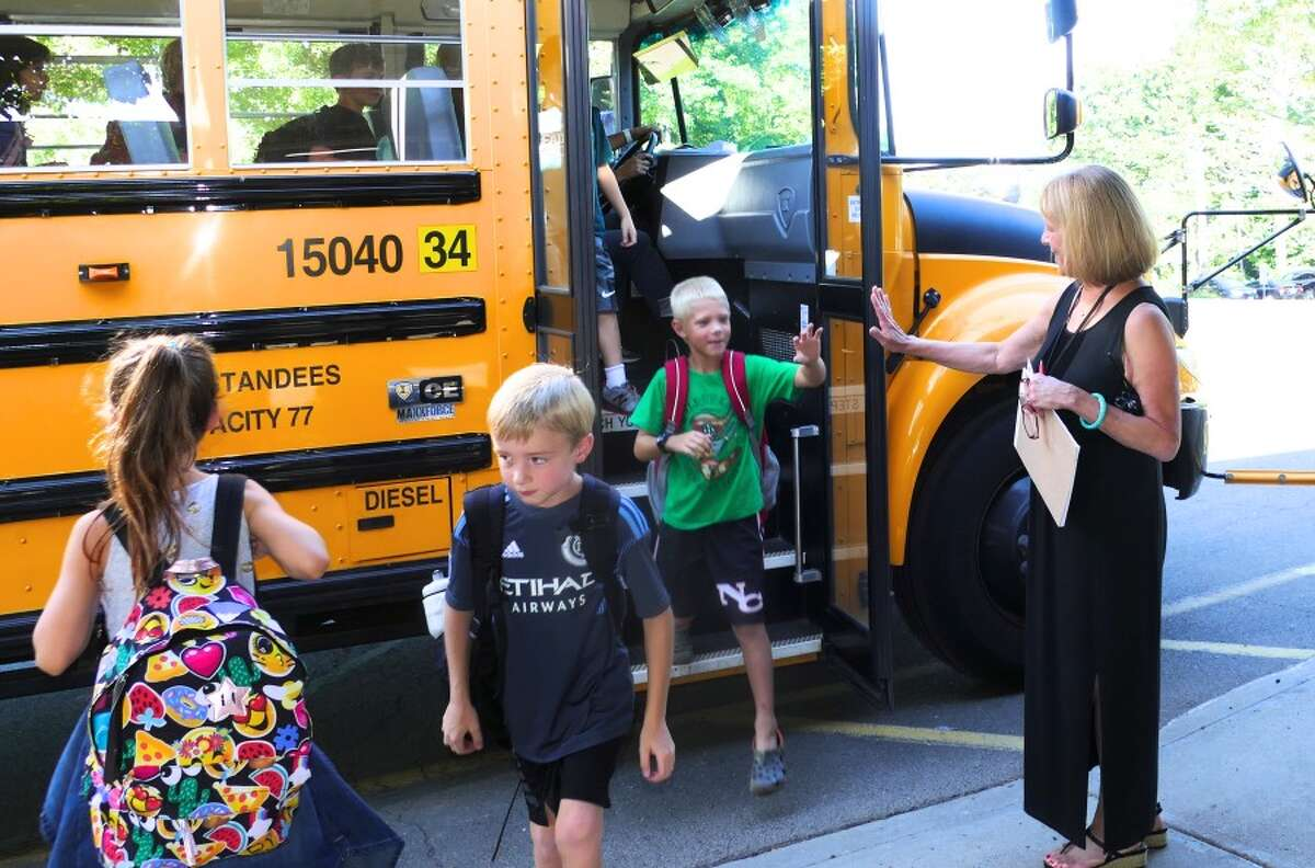 Principal Jan Murphy high-fives students as they get off the bus for their first day at West School. - Grace Duffield photo