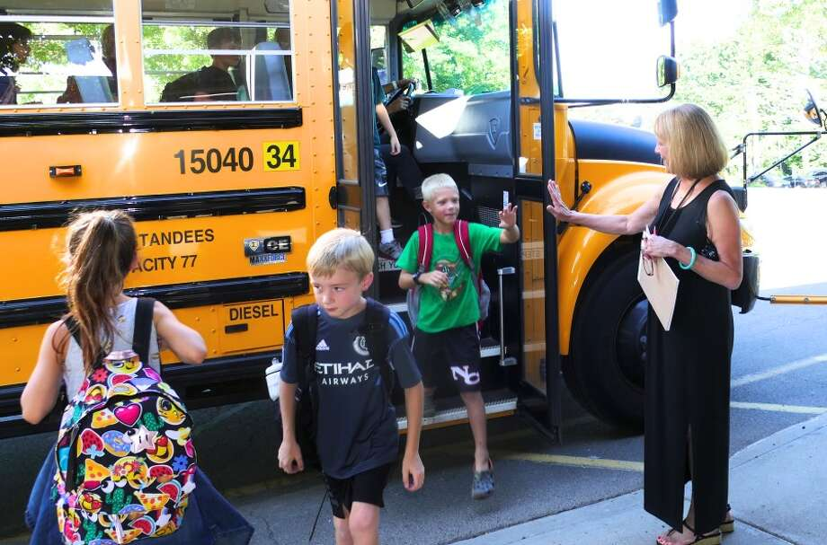 Principal Jan Murphy high-fives students as they get off the bus for their first day at West School. — Grace Duffield photo
