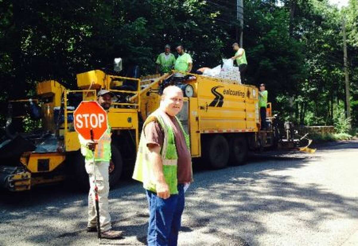 Kenny Arnow, Department of Public Works Highway Department, stands in front of his paving crew as they worked to lay a new pavement surface. - Greg Reilly photo