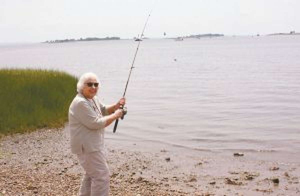 Adult Day Program participant, Eleanor, casts a line off the shore of Calf Pasture Beach during a recent fishing trip organized by Waveny LifeCare Network. - Contributed photo