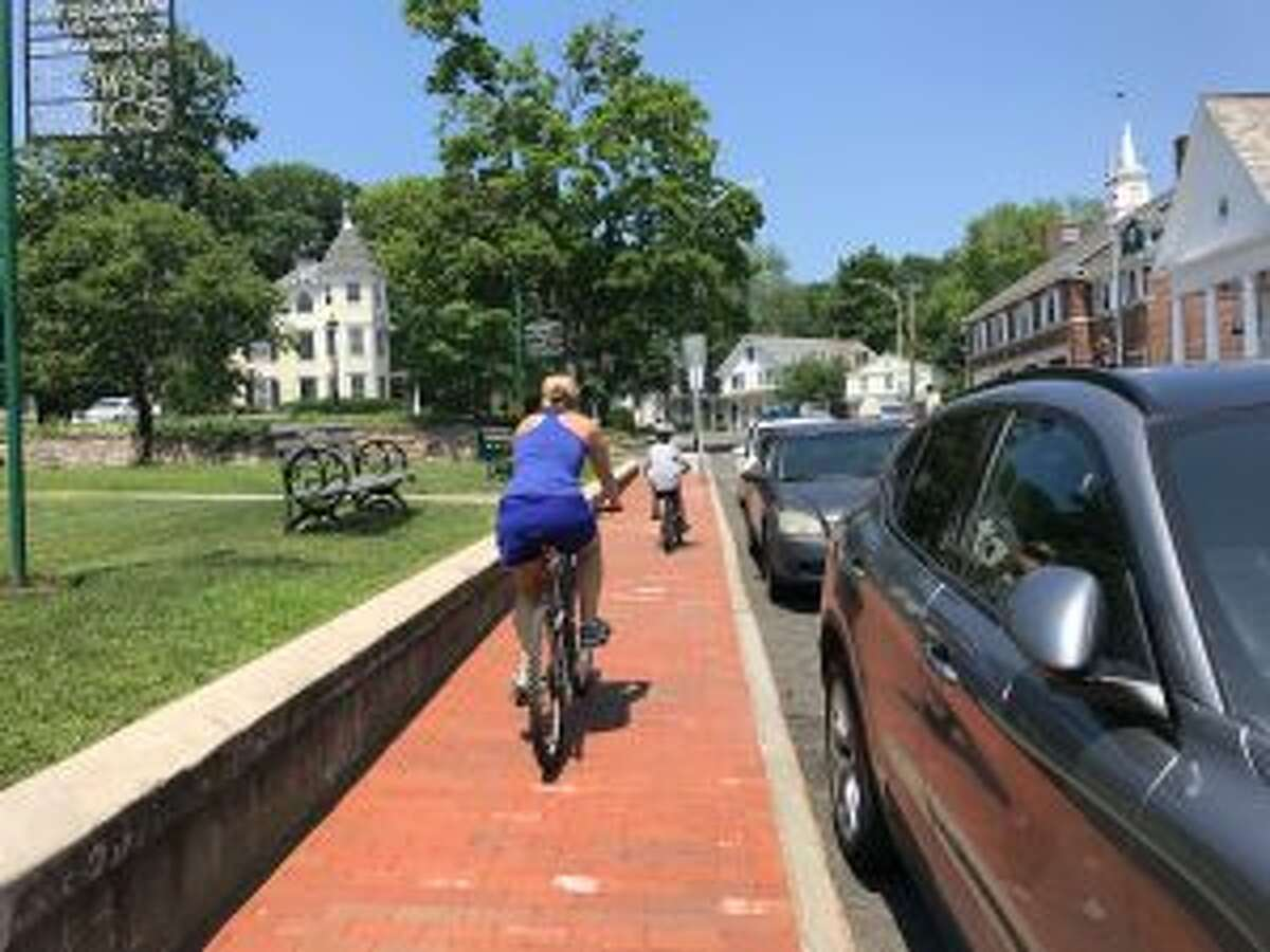 New Canaan: Safe bicycling in New Canaan is important. A woman and child improperly riding bikes on a sidewalk in the downtown area on July 2. - Sarah Klearman photo