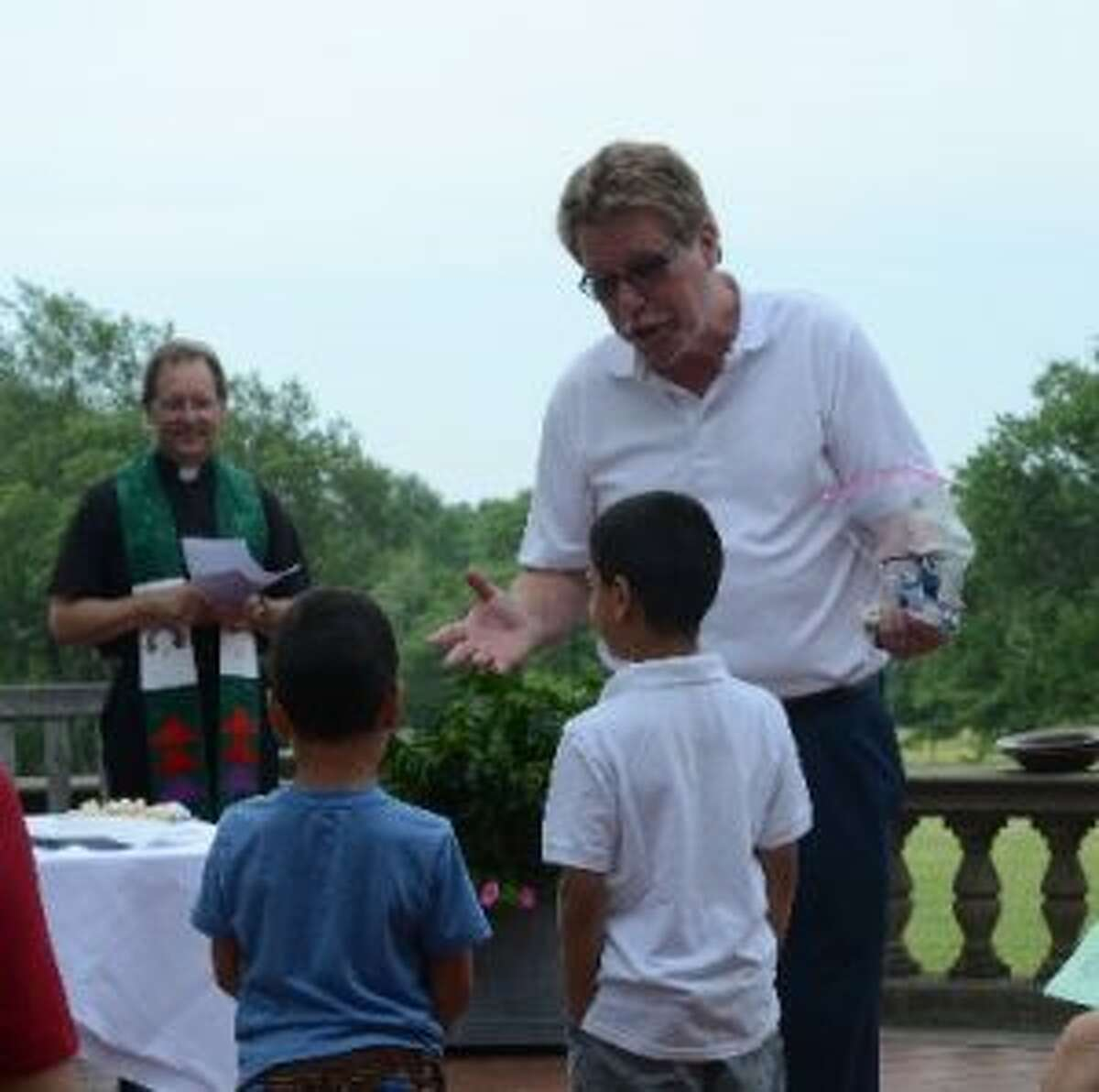 Pastor Eric Fjeldal talks to children about building the world with love, as Rev. Derrick Fallon looks on. - Greg Reilly photo