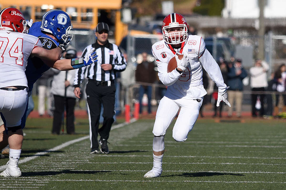 New Canaan Sikorski Award winner Sean Knight picks up some yards after an interception during the Rams' 27-0 Turkey Bowl win over Darien in November. - Dave Stewart photo