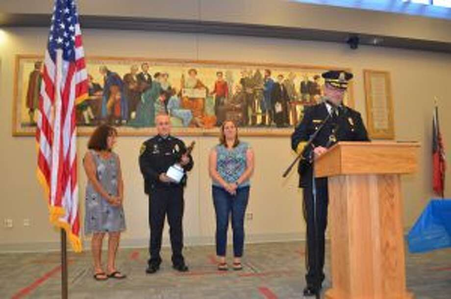 Resounding applause echoed in the room as Ofc. Tom Callinan was awarded the Lt. Stephen W. Wood Officer of the Year Award for 2017. Callinan, who was associated with over 1,200 incidents during 2017, was one of 12 officers in the New Canaan Police Department who received awards during their annual ceremony Tuesday evening. Tom Callinan with the Officer of the Year trophy, named after Lt. Stephen W. Wood. With Callinan are the late Lt. Wood's widow, Pat Wood, and daughter, Kim Wood. — Luca Triant photo