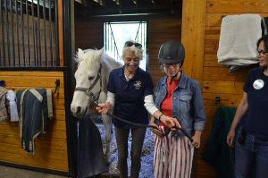 A program leader and participant directing a horse inside the barn. — Luca Triant photo
