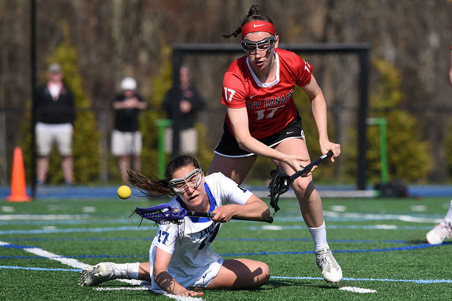 New Canaan's Julia Ozimek knocks the ball away from Darien's Sarah Jaques during Saturday's game at DHS. — Dave Stewart photo