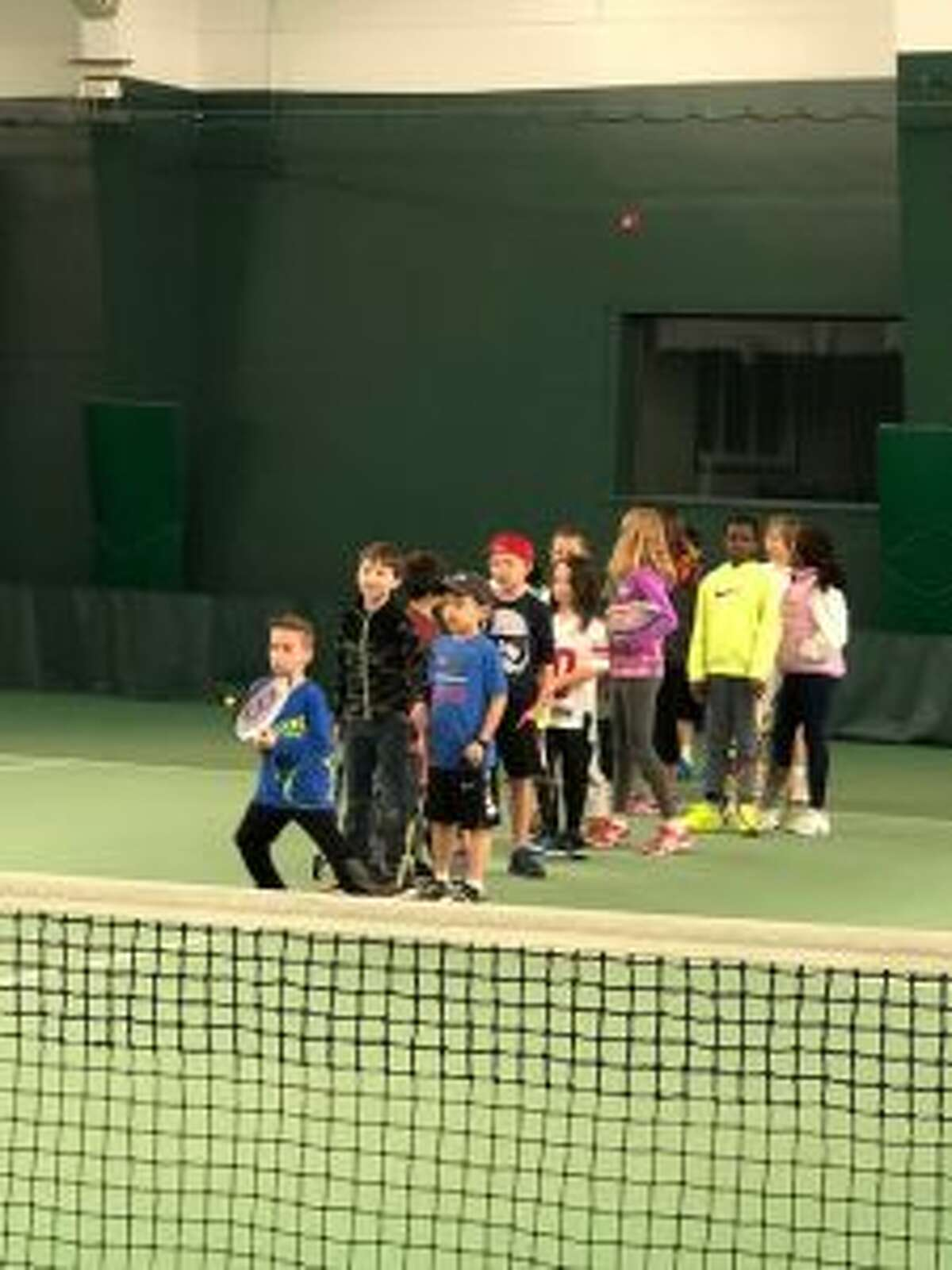 New Canaan: Pros recently competed, and kids played tennis for local charities. Kids play an interactive game at the charity tennis event. - Contributed photo
