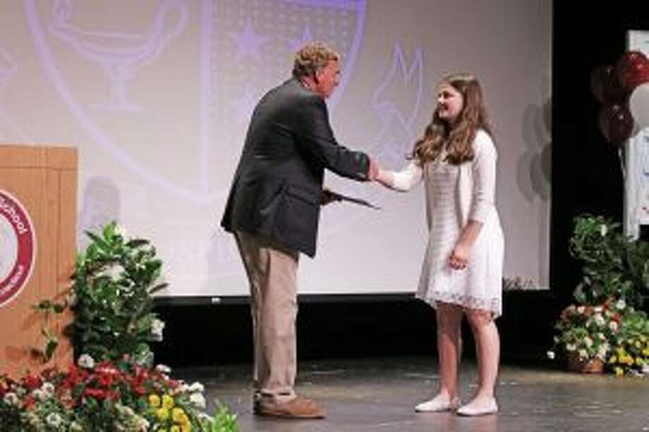 St. Luke's Head of Middle School Gareth Fancher gives Freya Young of New Canaan her certificate of promotion at the school's 8th Grade Promotion Ceremony. — Photo by Valerie Parker
