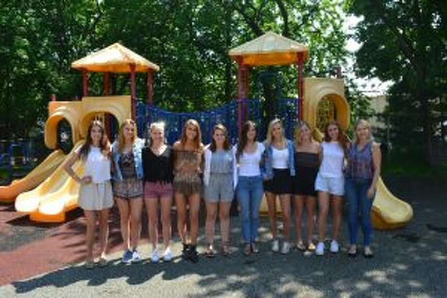 Interns from New Canaan High School are working on restoring the playground at the Carver Center, and raising funds. New Canaan High School interns, from left, Jackie Newlin, Alana Tonghini, Grace Brady, Becca Walshin, Erin McGoldrick, Maeve Selvaggi, Josie Bossidy, Brooke Deane, Kelsey Johnson with Carver volunteer Janine Smith, far right, stand in front of the current playground at the Carver Center that needs replacing. — Contributed photo