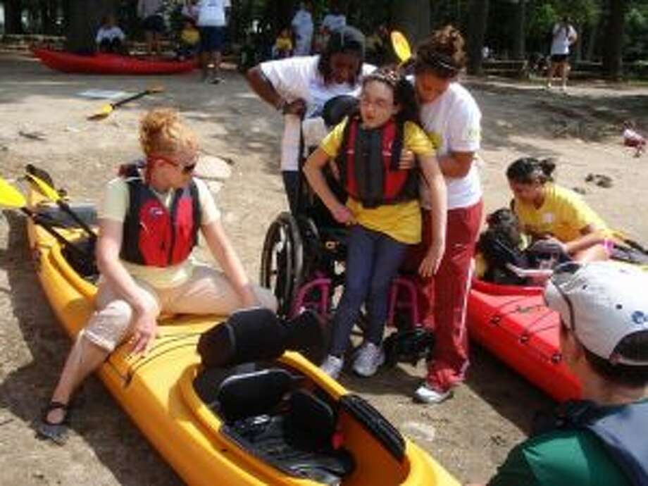 New Canaan: STAR offers rock climbing, kayaking for youth, and young adults with disabilities. Volunteers help class participants prepare for a kayaking adventure.— Contributed photo