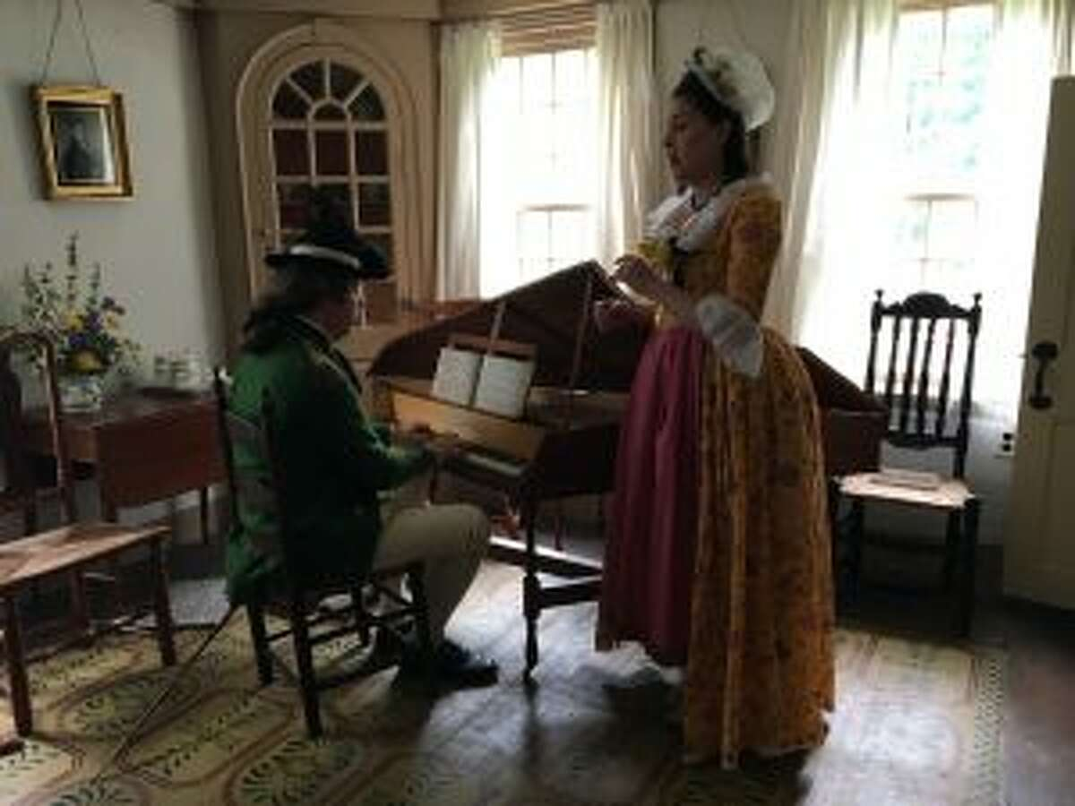 Two reenactors, in costume, perform a song on a harpsichord. - Luca Triant photo