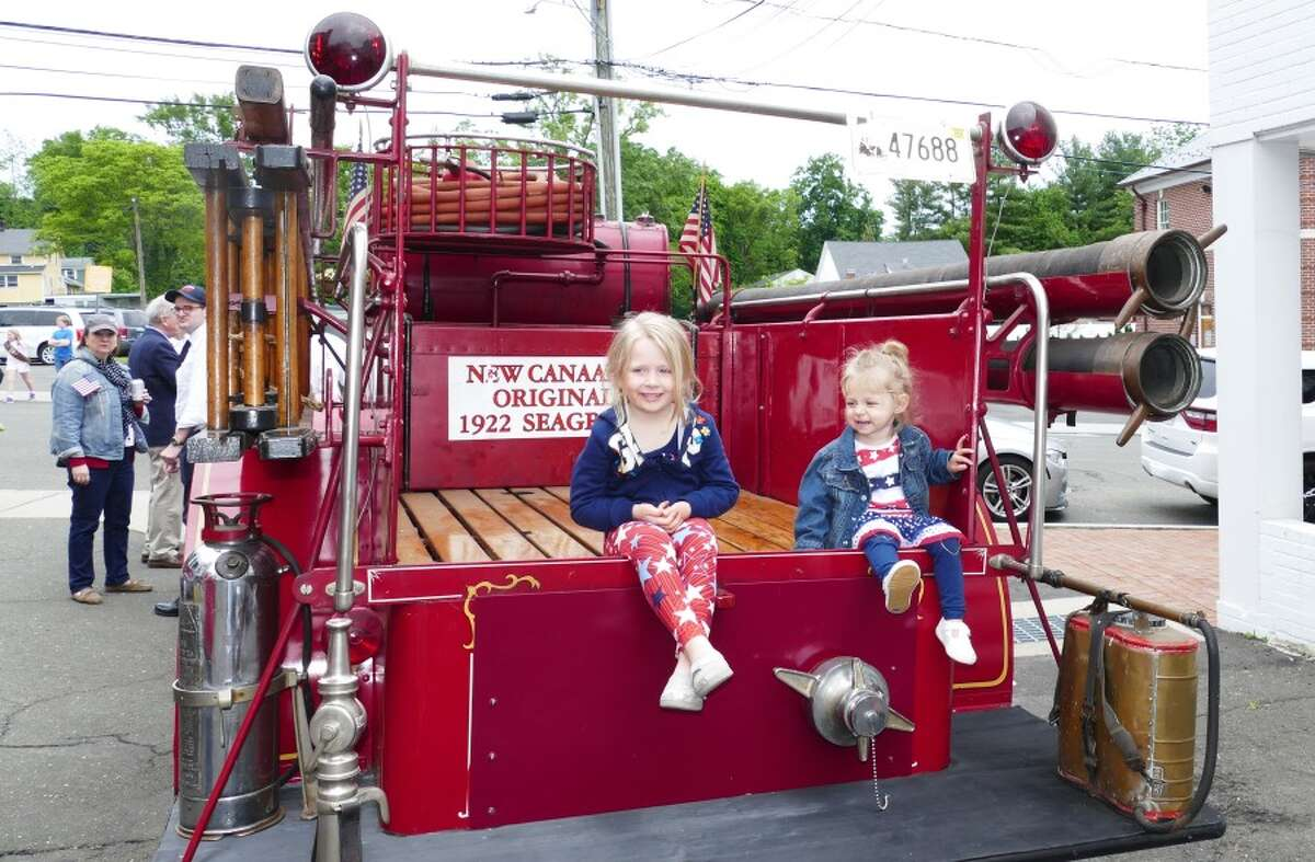 Madison and Jordyn Noble sit on the back of the oldest New Canaan fire truck. - Grace Duffield photo