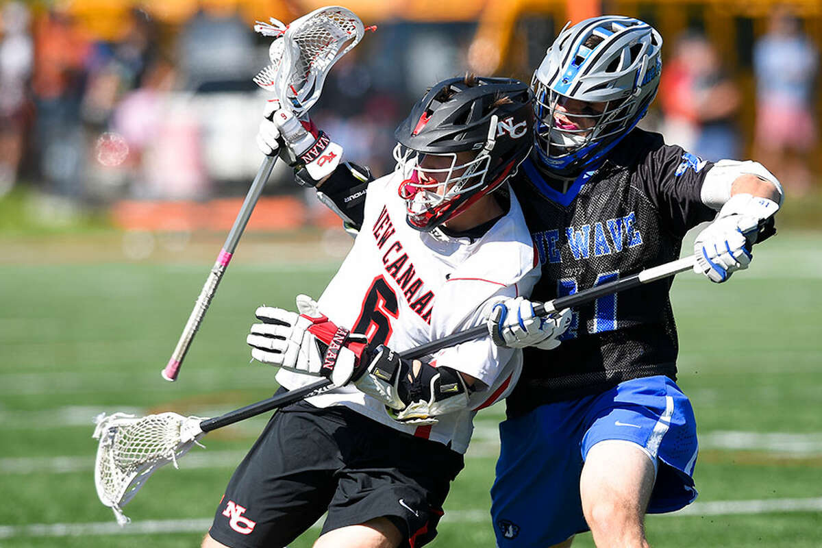 New Canaan's Teddy Manges (6) battles Darien's Pierce Hoyda (41) in a boys lacrosse game at Dunning Field on Saturday. - Matthew Brown/Hearst Connecticut Media