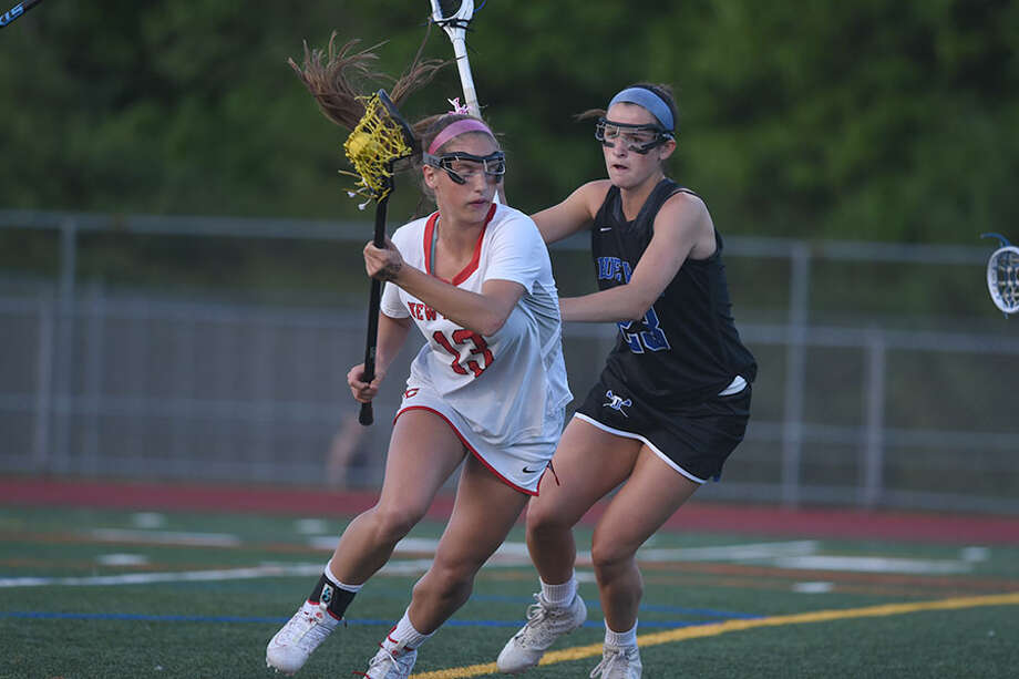 New Canaan's McKenna Harden (13) looks for room to move while Darien's Maddie Joyce (23) defends during the FCIAC girls lacrosse final Wednesday night at Testa Field in Norwalk. — Dave Stewart/Hearst Connecticut Media