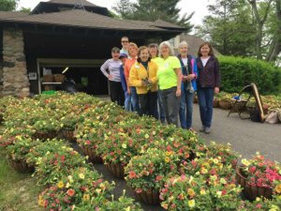 New Canaan Beautification League members at Irwin Park preparing hanging baskets to be displayed around the downtown village. — Contributed photo