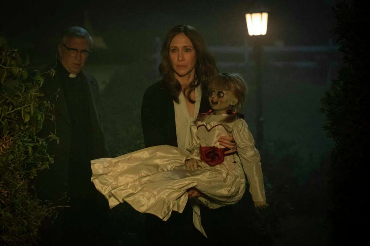This image released by Warner Bros. Pictures shows Vera Farmiga, center, in a scene from the horror film, 'Annabelle Comes Home.'