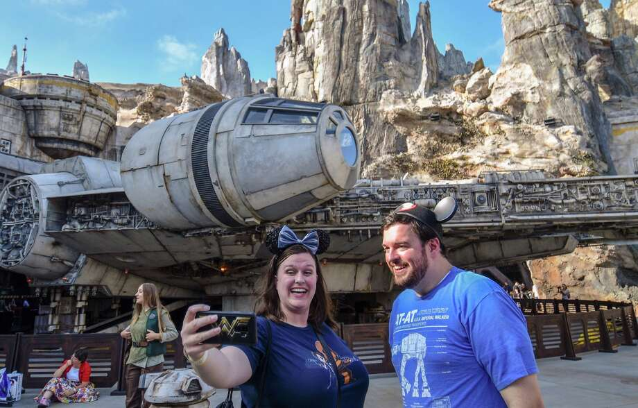 Disney fans take selfies in front of the Millennium Falcon on opening day at Star Wars: Galaxy's Edge at Disneyland in Anaheim, CA, on Friday, May 31, 2019.