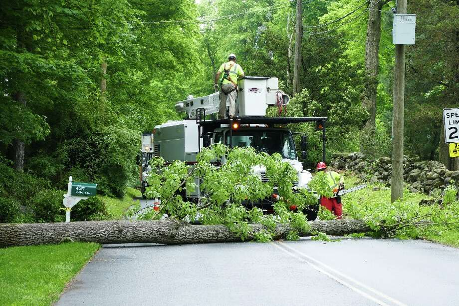 Workers at 10 a.m. cut up the tree that fell across Valley Road earlier Wednesday morning and took out electrical power for customers in New Canaan and Wilton. — Luca Triant photo